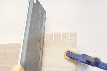 slots being cut into a square of plywood held by a vise