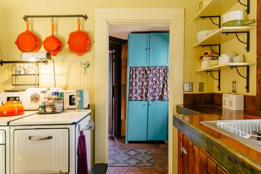 A colorful, vintage kitchen with yellow walls, retro stove and orange-blue accents