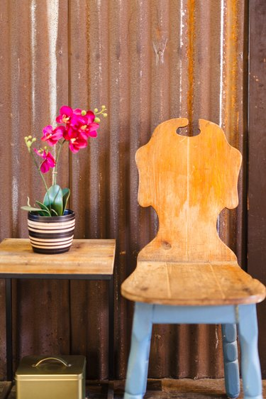 A vintage wood chair with blue legs next to a side table with pink orchids