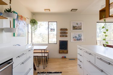 Kitchen with white cabinets, hairpin leg dining furniture, hanging plants, wood shelves, and wood floors.