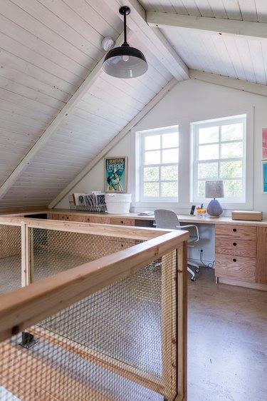 An office loft with a wood-mesh wall. A Scandinavian style wood desk and a black bell pendant light.