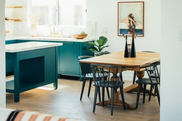 teal eat-in kitchen with wood table and black chairs