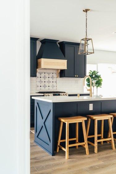 Dark blue kitchen cabinets, ornate backsplash, kitchen island with wood stools, gold lantern pendant light.