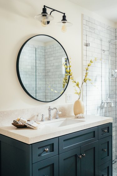 Bathroom with blue painted cabinets, white sink, round mirror, and black and glass lighting fixture. Ceramic vase on sink.
