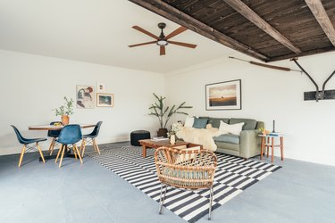 Living room in a California-bohemian style contemporary apartment: cement floor, wood ceiling, ceiling fan, black and white rug, rattan accent chair, plant, coffee table and couch