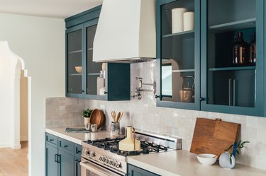 Kitchen stove with white hood, ceramic square tile, cream countertops, and blue green painted cabinets. Open cabinetry on top.