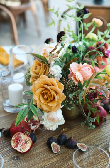 a floral centerpiece with yellow, pink, and white flowers