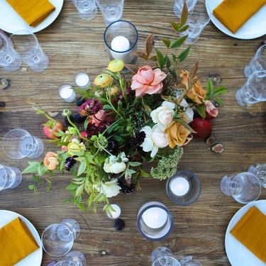 a rustic wooden table with a large floral centerpiece