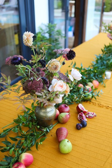 a gold-colored table with a runner made from greenery, flowers, and fruit