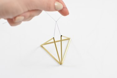 Geometric gold twig ornament with black thread