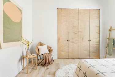 Bi-folding closet, accent chair with white pillow, neutral throw, wood stool with vase of flowers, abstract wall hanging