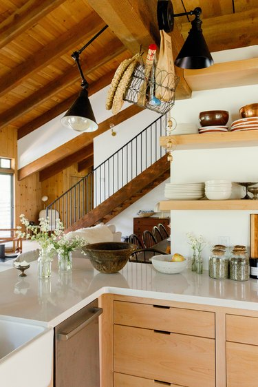 Kitchen with wood shelves, white counter, wood cabinets. Vases of flowers and black lamp sconces. A wood staircase in the distance.