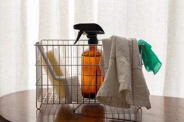 metal basket filled with spray bottle, scrub brush, sponge, and dish rags