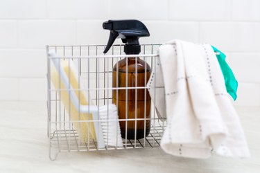 A metal basket with washcloth, gloves, spray bottle, sponge, and brush
