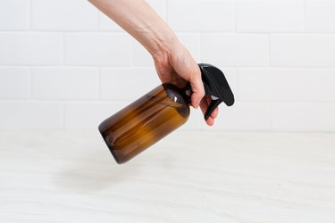 A hand holding a spray bottle