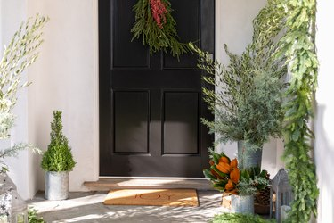front door christmas decorations with red and green door swag and fresh greenery