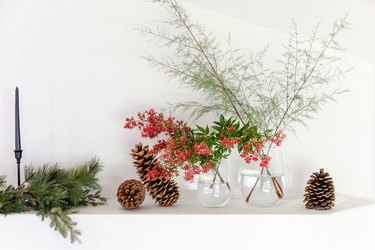 fresh red flowers in clear glass vases on mantel with pinecones and winter greenery