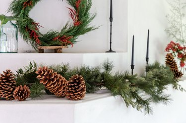 Red and green Christmas colors with garland on mantel with black taper candlesticks and fresh flowers