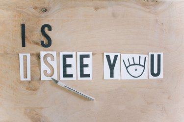 "creating templates for the ""i see you"" message by cutting printed letters with a utility knife"