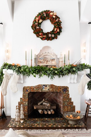 Holiday mantel with garland, wreath, candles, and stockings