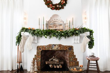 fireplace featuring holiday garland, decor, candles, and holiday wreath