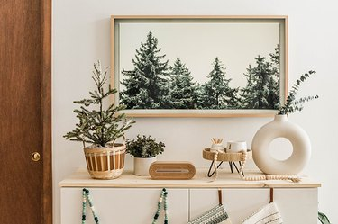 Pine tree wall art with circular white vase and modern decor touches