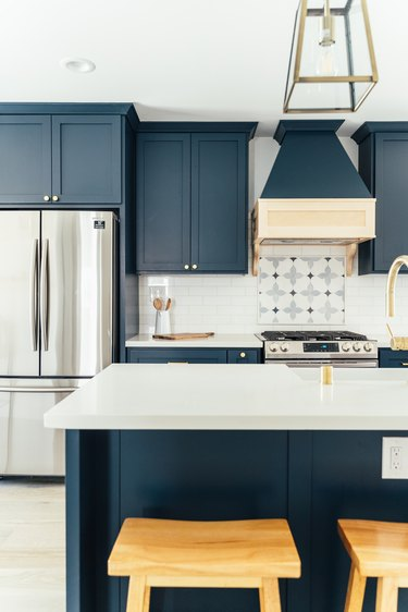 Kitchen with dark blue cabinets, French refrigerator, ornate backsplash by stovetop, kitchen island with wood stools, lantern pendant light