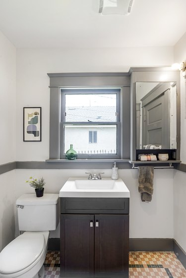 Bathroom with neutral black tile flooring, small vanity and gray accents