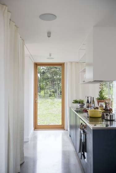 a long narrow kitchen island with a glass door to the outside