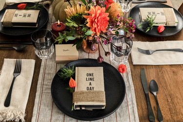 fall party idea with journal party favors on black plates and floral, pumpkin decor
