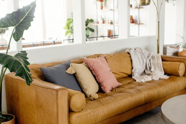 Brown leather couch with neutral throw pillows