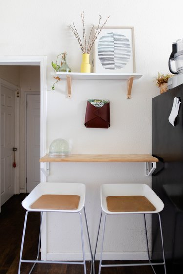 White stools and wood shelving with plants and art