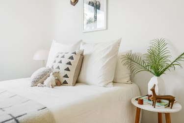 White bedding, black-white patterned pillows, stuffed animal and blanket. Stool with geometric vase of palm leaves and a sculpture