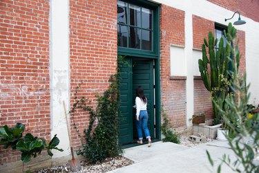 Woman walking through green door of brick building