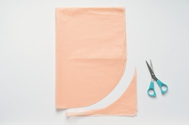 Cut curved tissue paper with turquoise-handled scissors against a white background