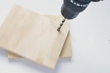 holes being drilled into a square of plywood