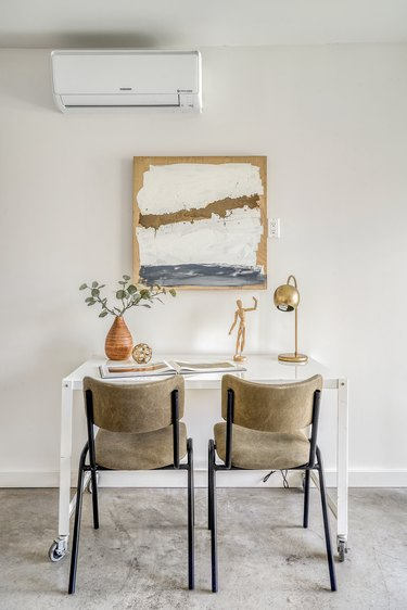 Two neutral-black chairs at a white desk. A vase with plant cuttings, a drawing figurine, a gold globe table lamp, and an abstract painting.