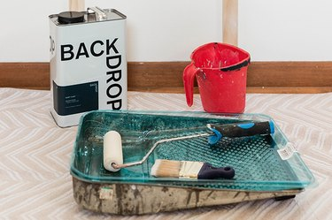 Paint tray, paint brush, paint roller, container of paint, and a paint bucket