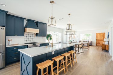 Kitchen with dark blue cabinets, kitchen island with wood stools, and gold lantern pendant lights