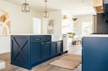 Dark blue kitchen island with gold lantern pendant lights. Light wood floor with beige striped rug.