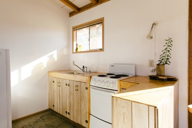 a kitchen with natural wood cabinets and an electric stove
