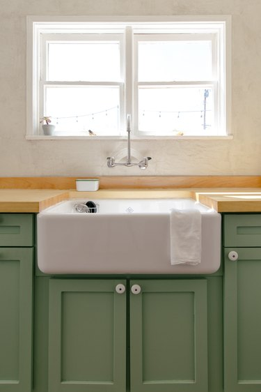 a kitchen includes a deep porcelain sink, green wooden cabinets, and a butcher-block counter