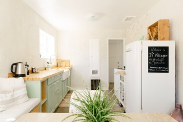 a narrow kitchen has a row of green cabinets on one wall, and the refrigerator and stove along another