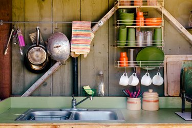 a small outdoor kitchen with wall-mounted racks for cups and plates and pots hanging from a rod