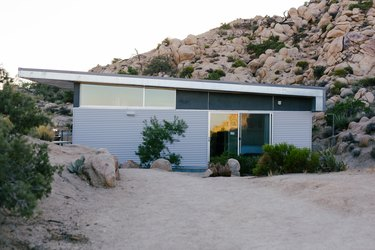 a pre-fab home with a glass and corrugated metal exterior