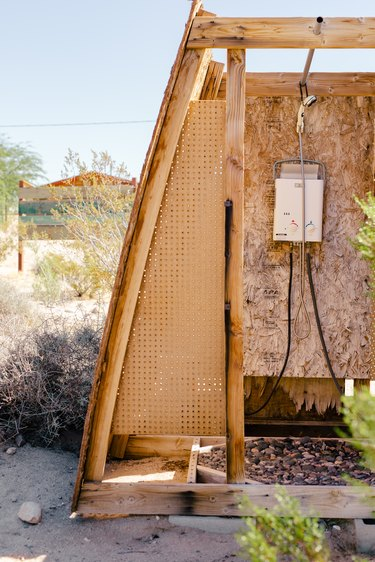 an outdoor shower structure made of plywood