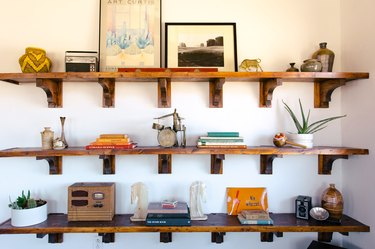 old books, vintage toys, and small pieces of art on rustic wooden shelves