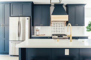 Dark blue kitchen cabinets with gold knobs. A silver French refrigerator. Ornate tile by stovetop. Kitchen island with gold sink faucet.