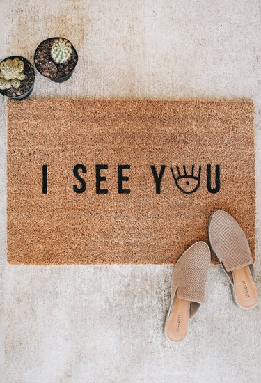"a woman's shoes on a brown doormat with black letter spelling ""out i see you""--the ""o"" in ""you"" is an eye graphic"