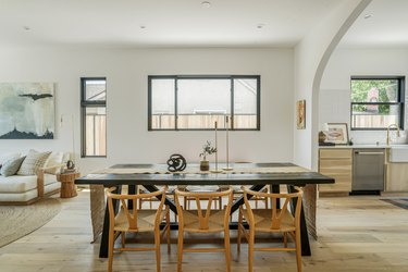 Black dining room table with honey-wood chairs, windows of varying sizes